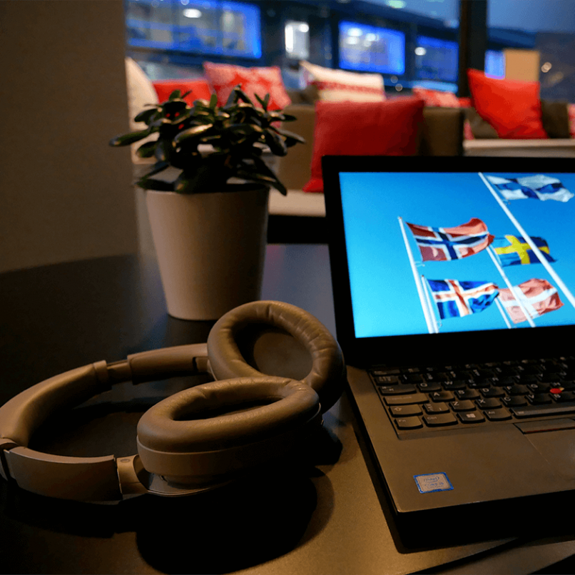 The picture shows a computer and headphones in a café.
