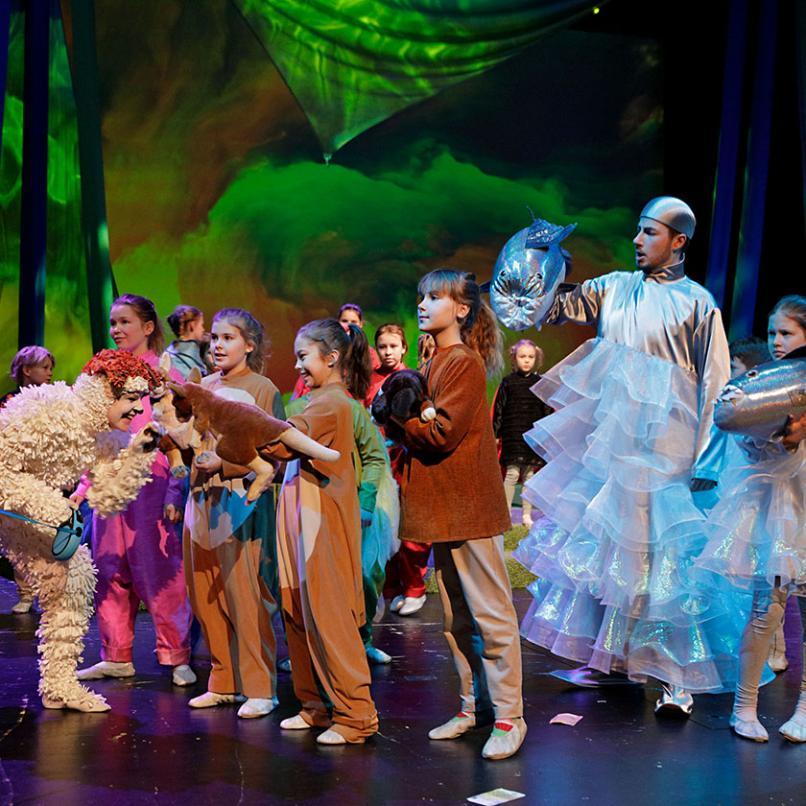 Bild med barn och elever som sätter upp operan Djurens planet.