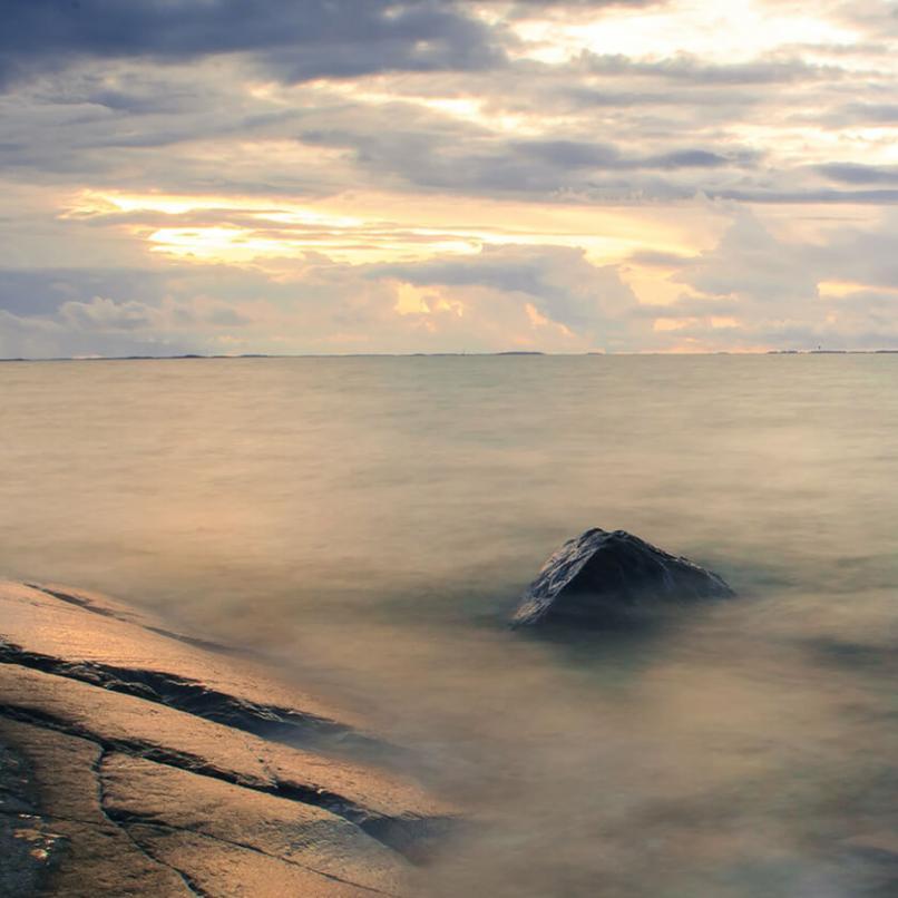 """Bilden visar hav och sten, presentationsbilld för för utställningen """"Välkommen hem - vi möts på mitten."""""""